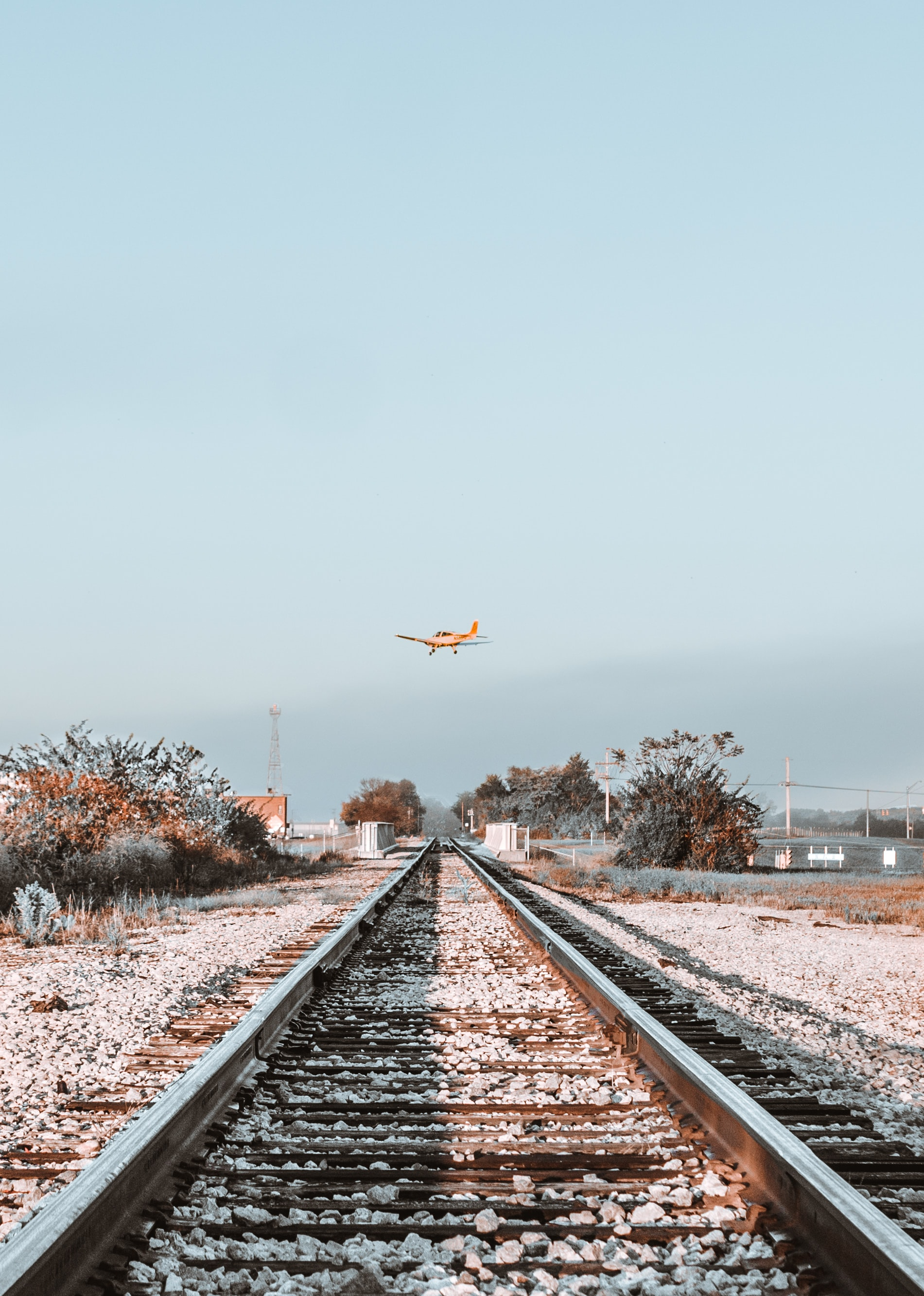 orange monoplane flying above a railroad
