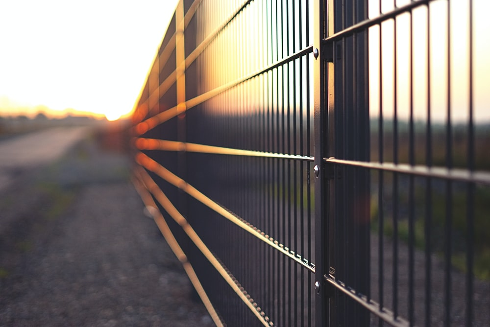 black metal fence during sunset