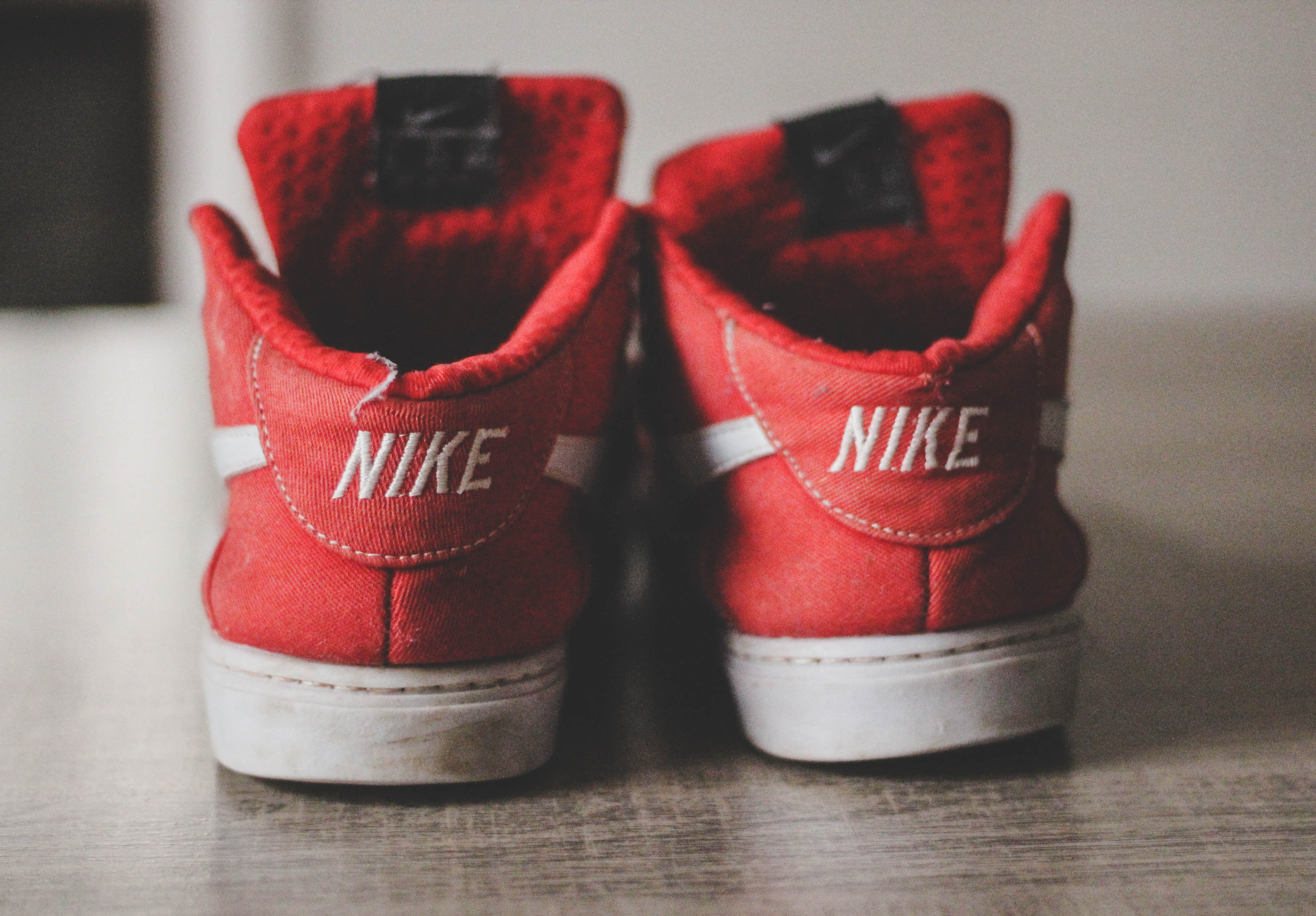 closeup photography of pair of red-and-white Nike low-top shoes
