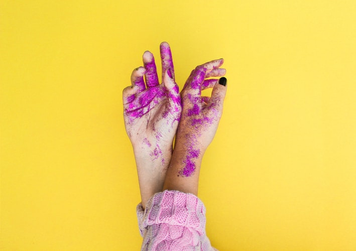 A yellow background with two hands extended across it, the hands are covered in purple glitter.