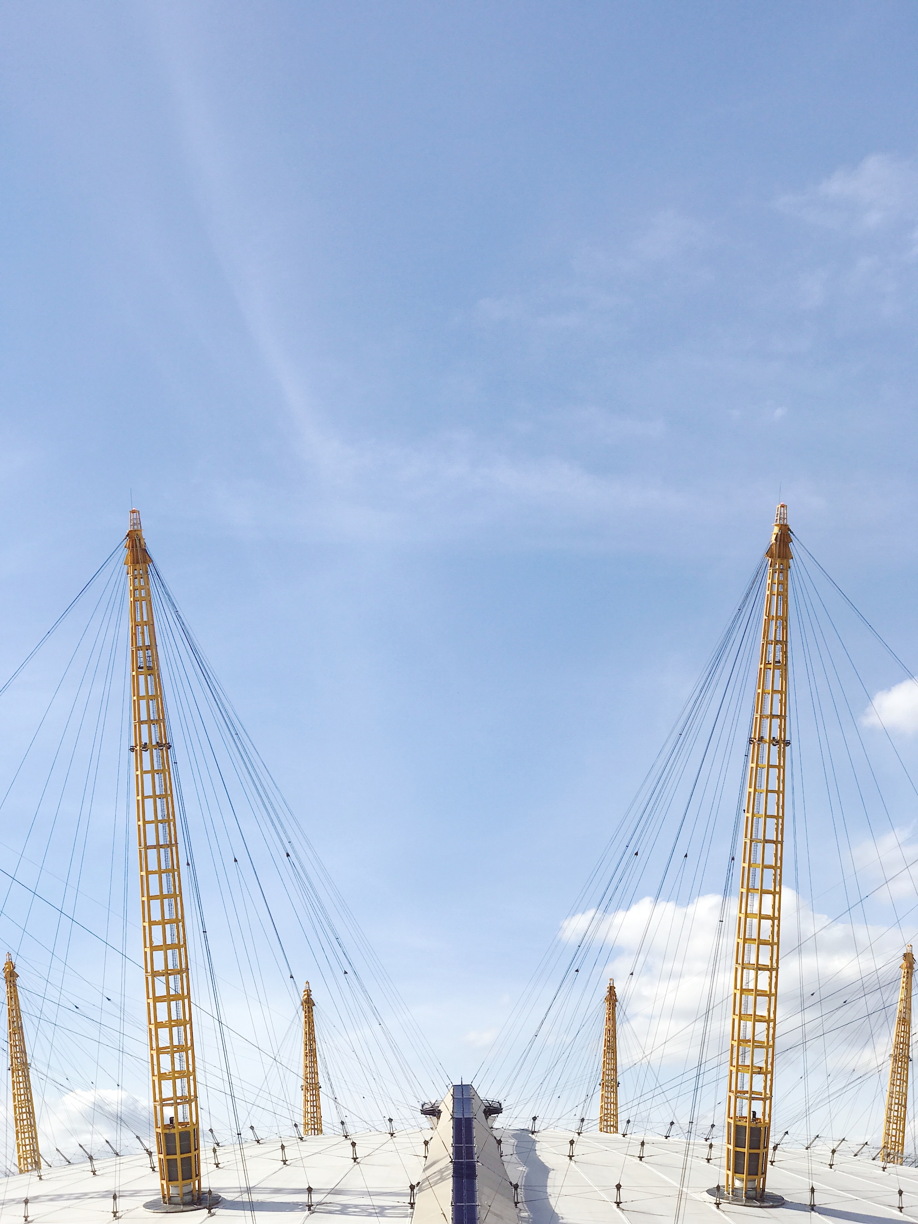 two yellow cable towers under blue sky