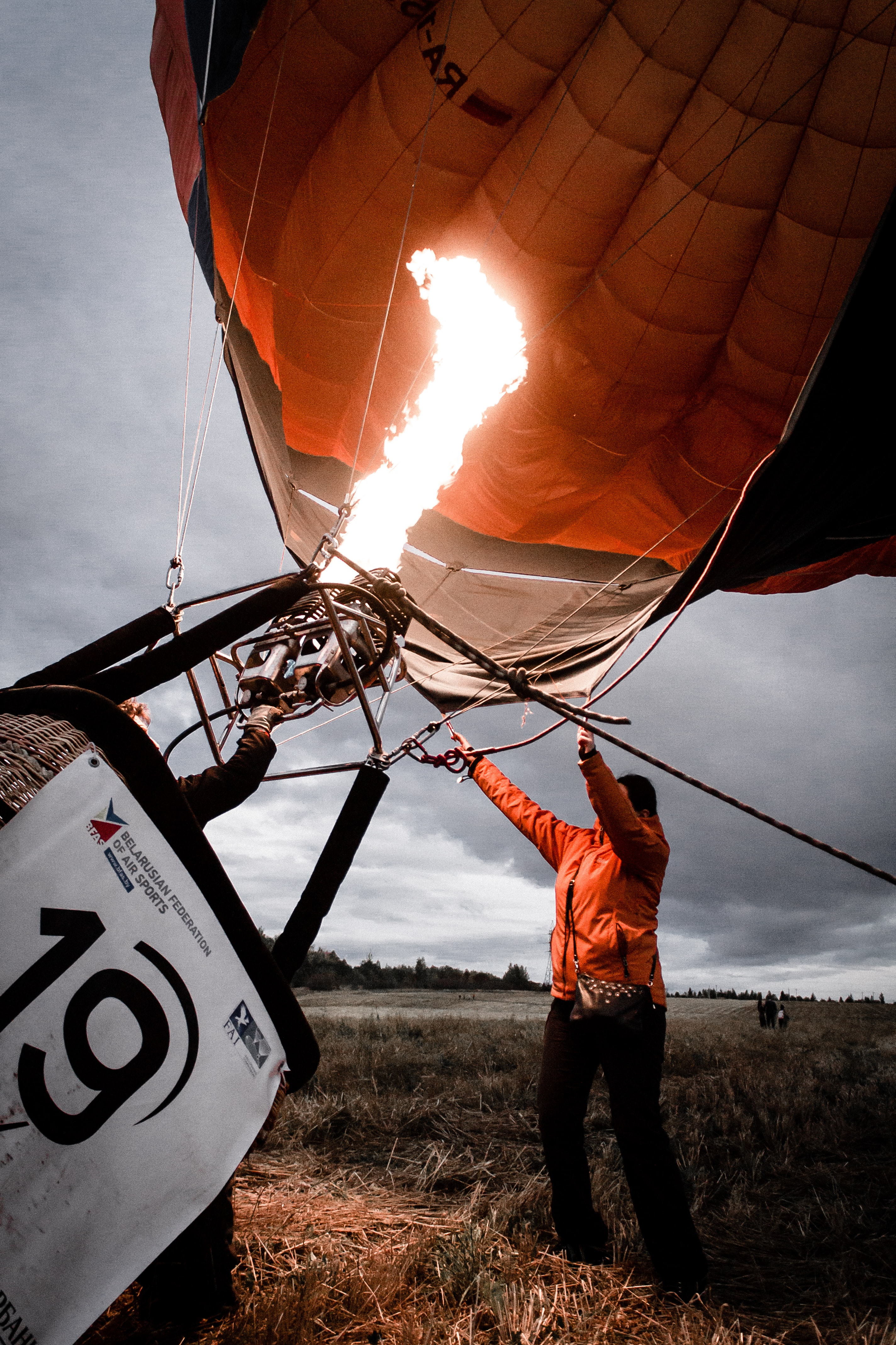 person arranging orange and black hot air balloon during daytime
