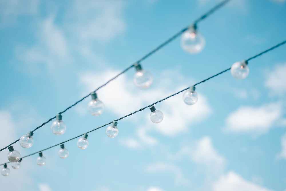 tilt lens photography of string lights under cloudy skies