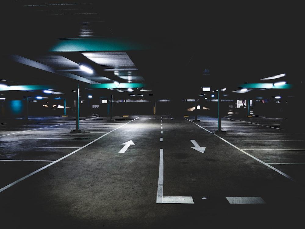 gray concrete parking area under blue building