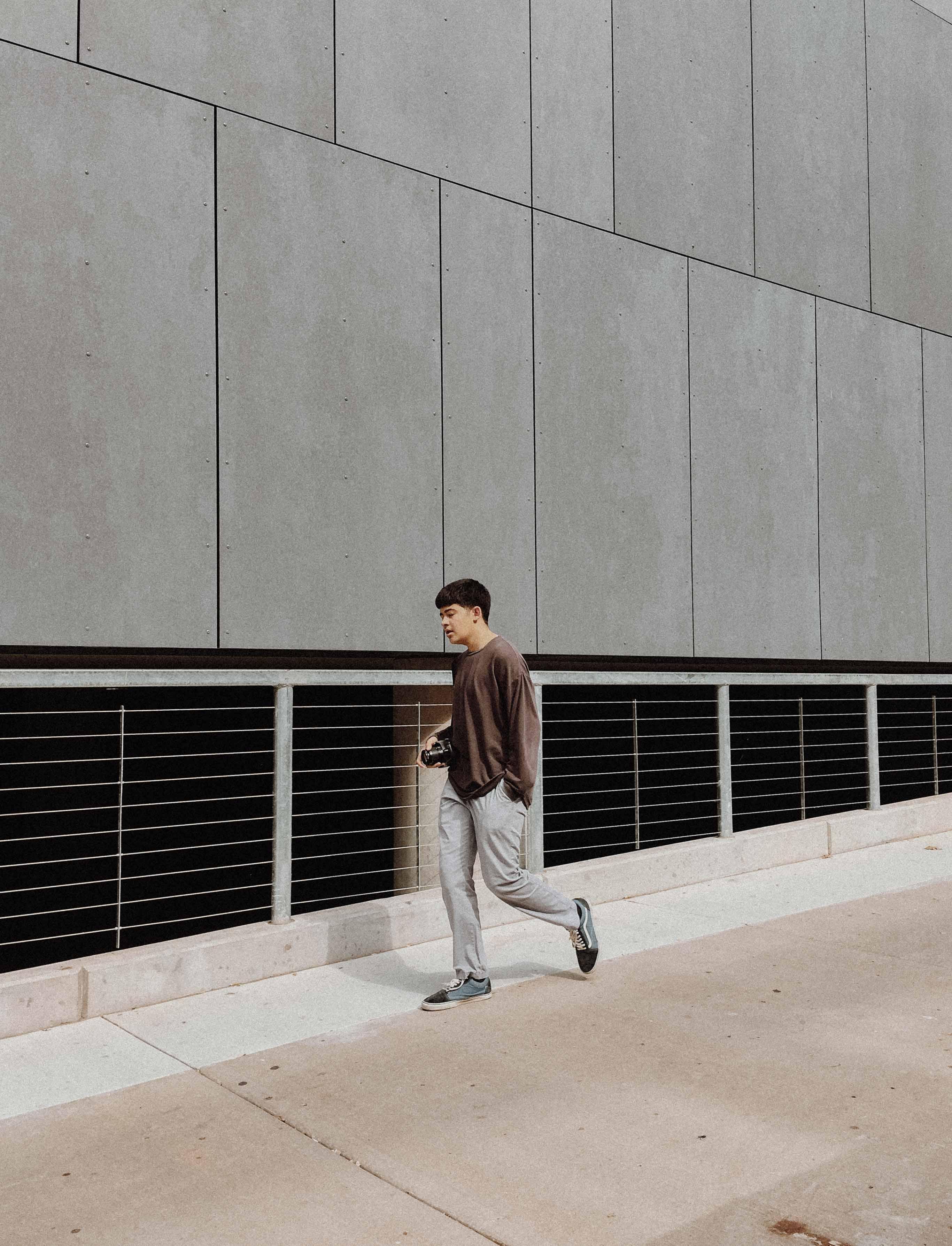 man wearing brown shirt standing near gray wall during daytime