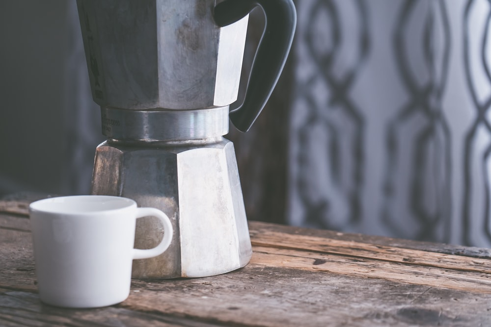 white mug beside moka pot