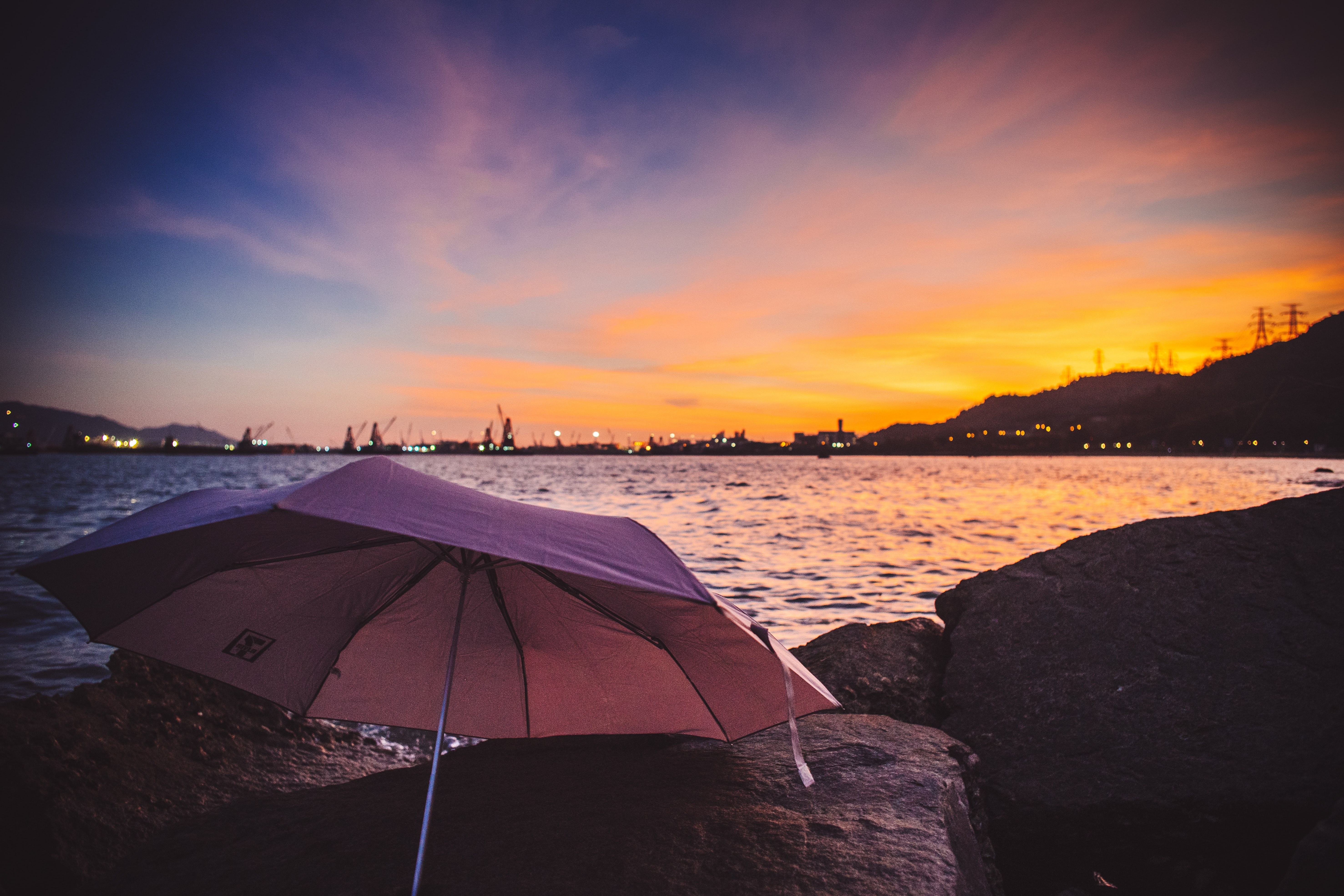 pink umbrella on stone near body of water at golden hour