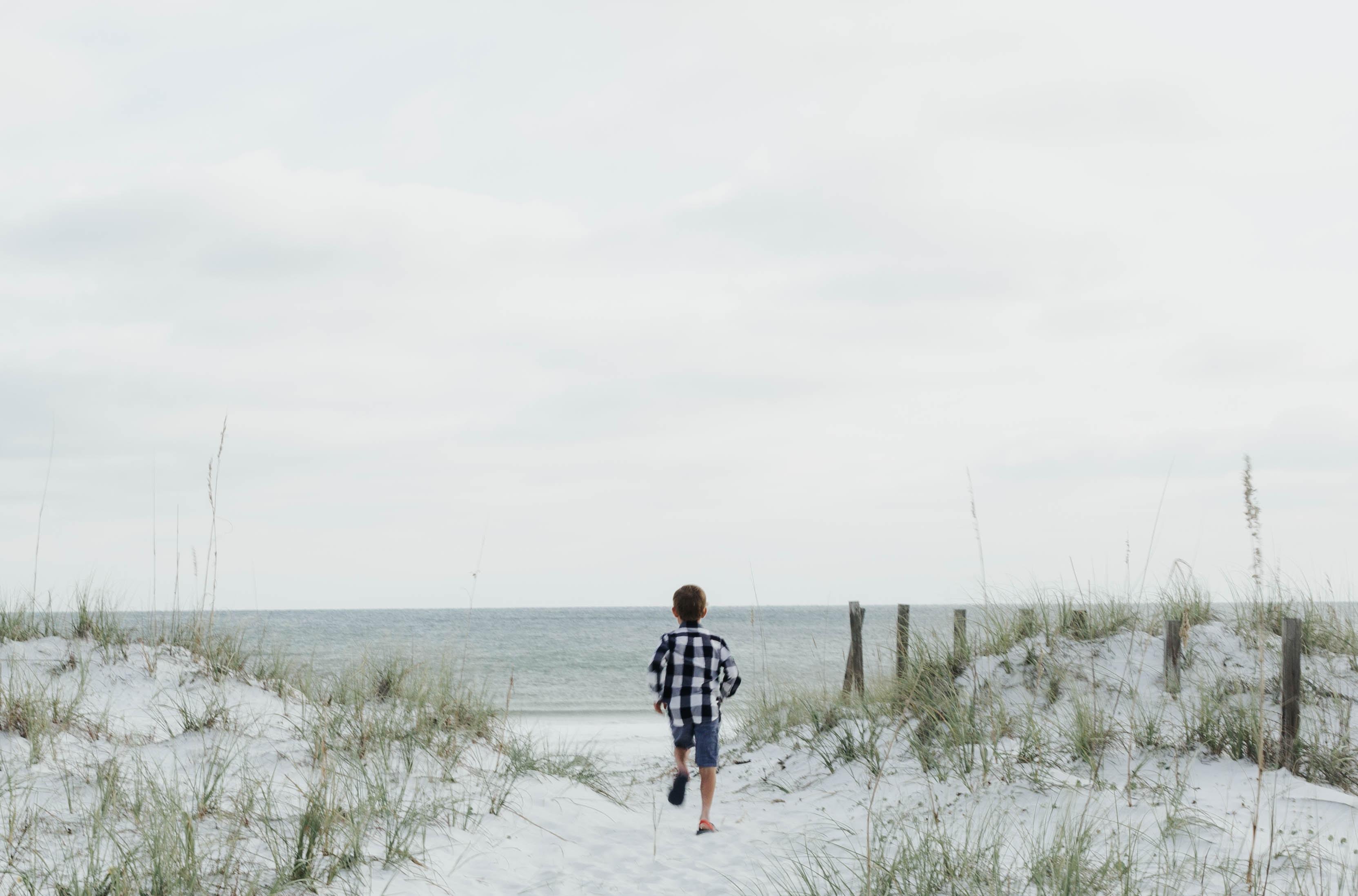 boy running near body of water