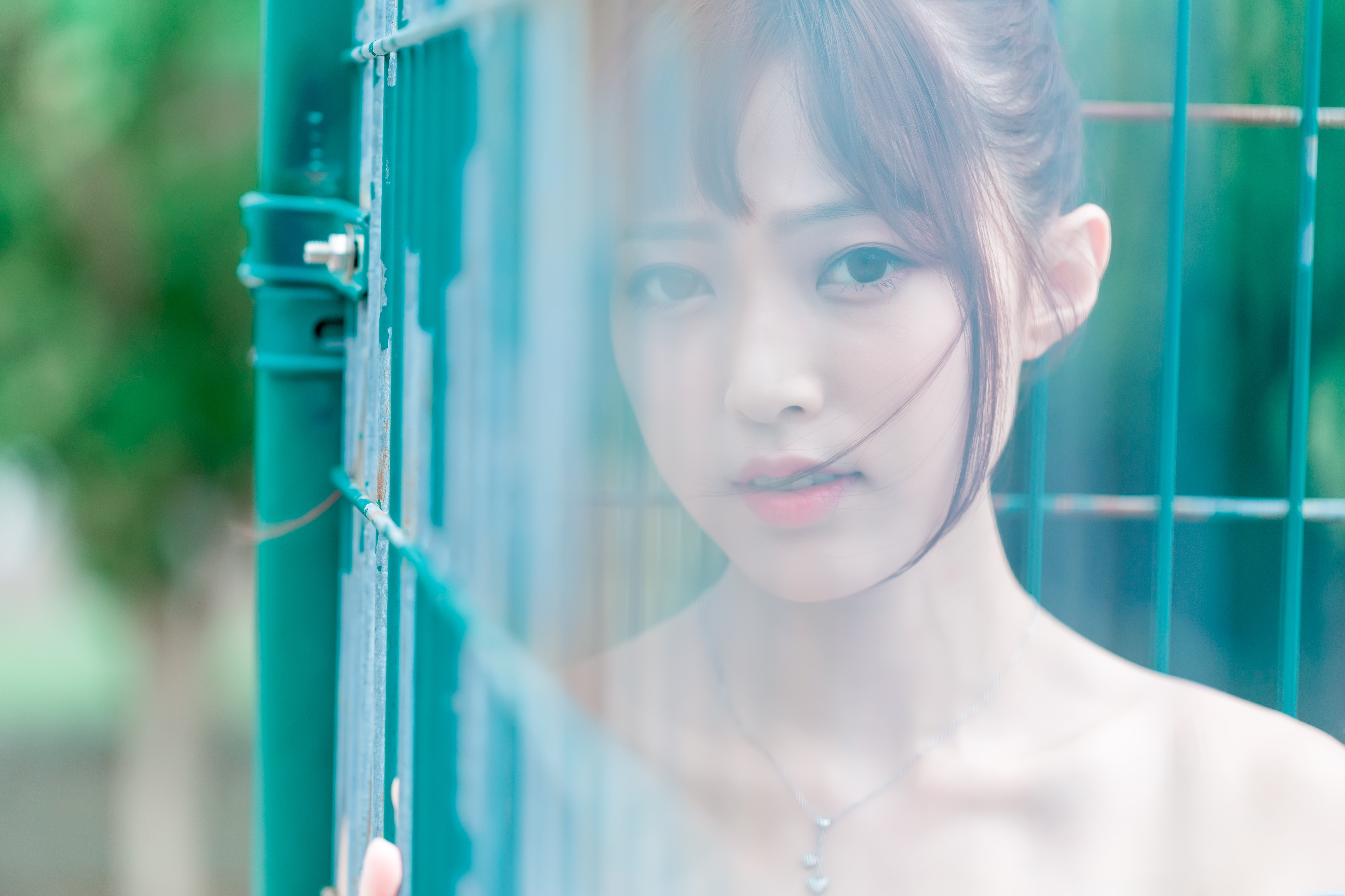 selective focus of woman face beside fence during daytime