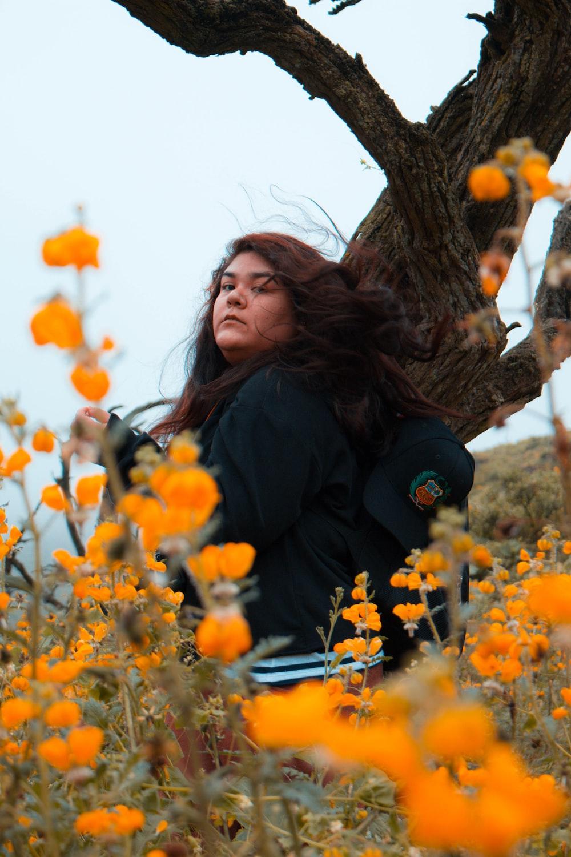 woman wearing black jacket between tree and flowers
