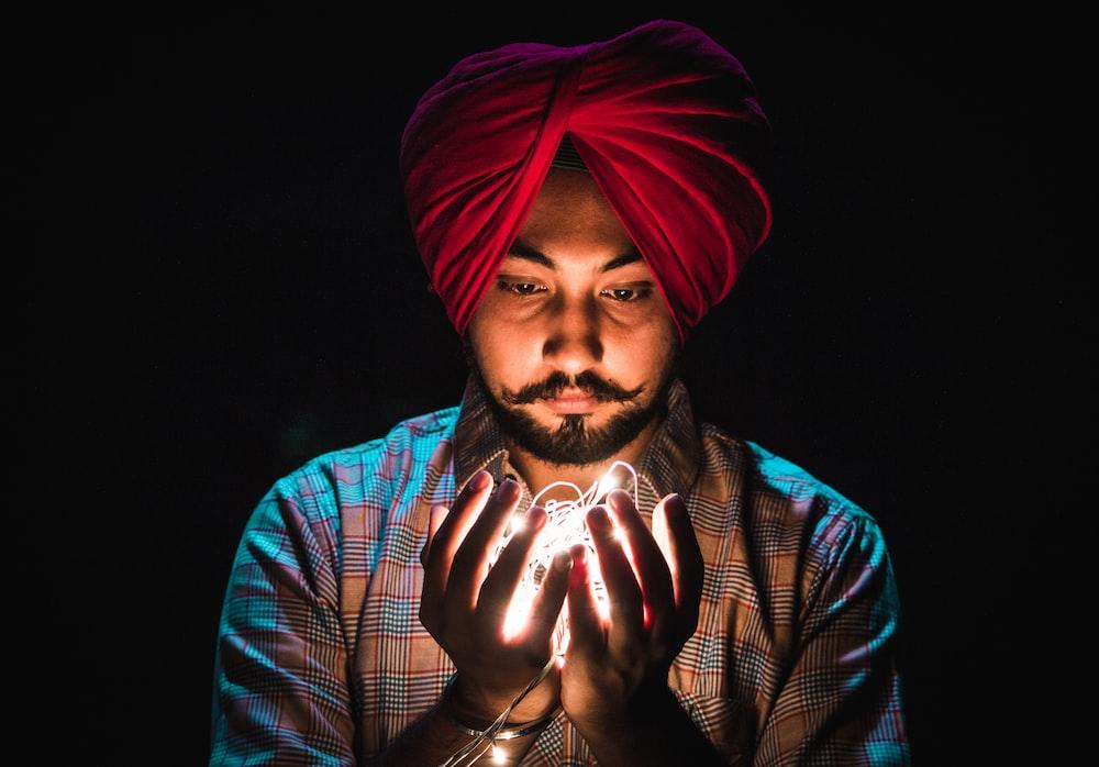 man holding string lights