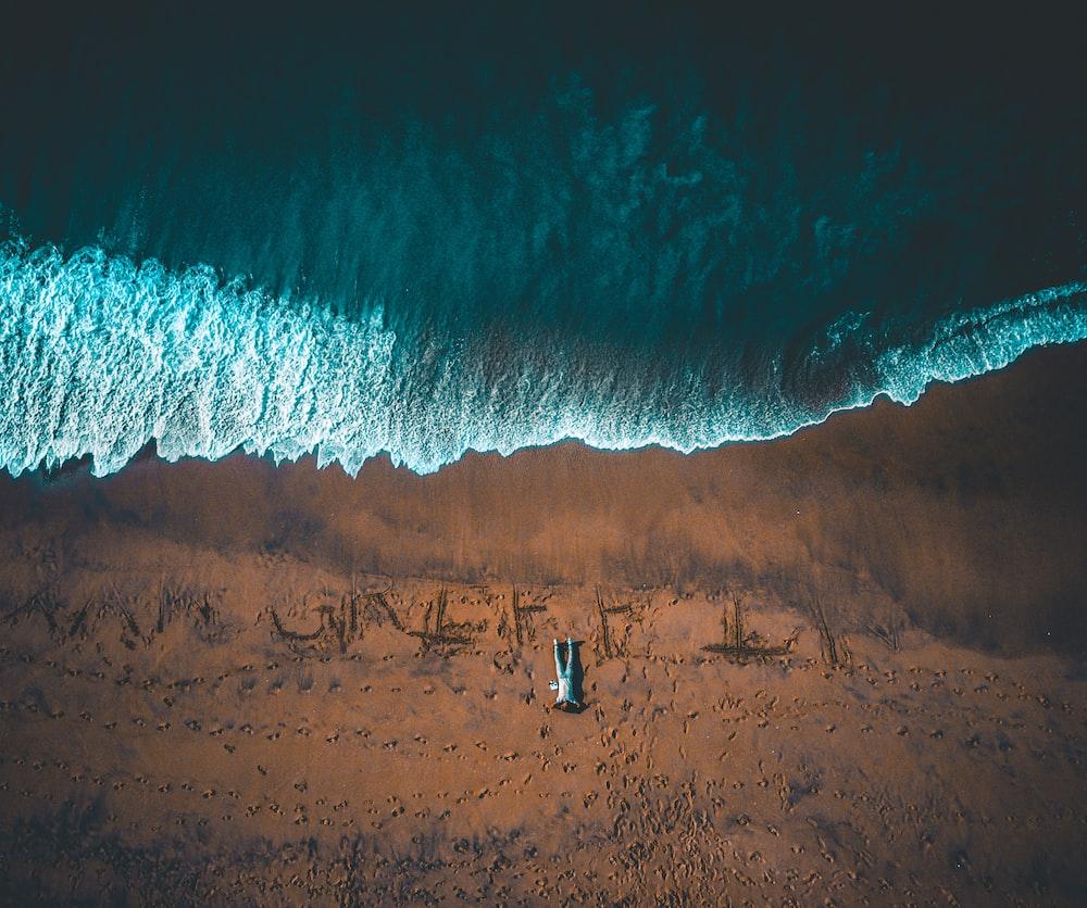 bird's eye view of man lying down on seashore