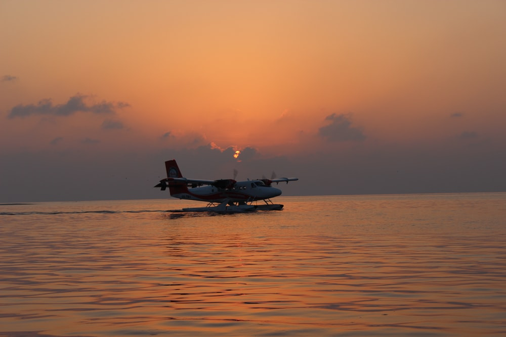 silhouette of plane on top of body of water during sunset