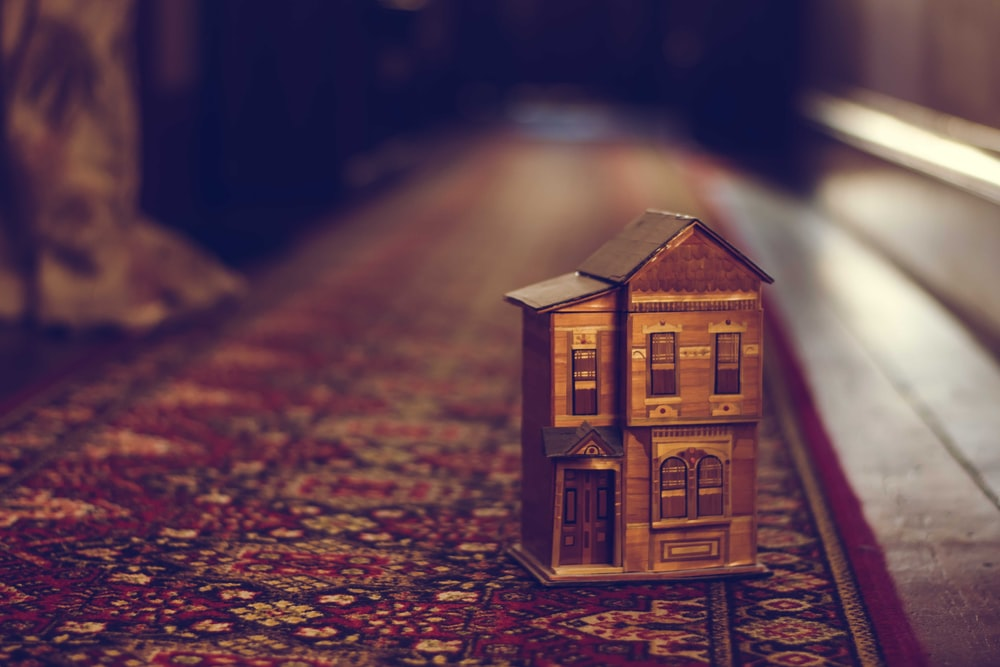 brown wooden house miniature on red carpet