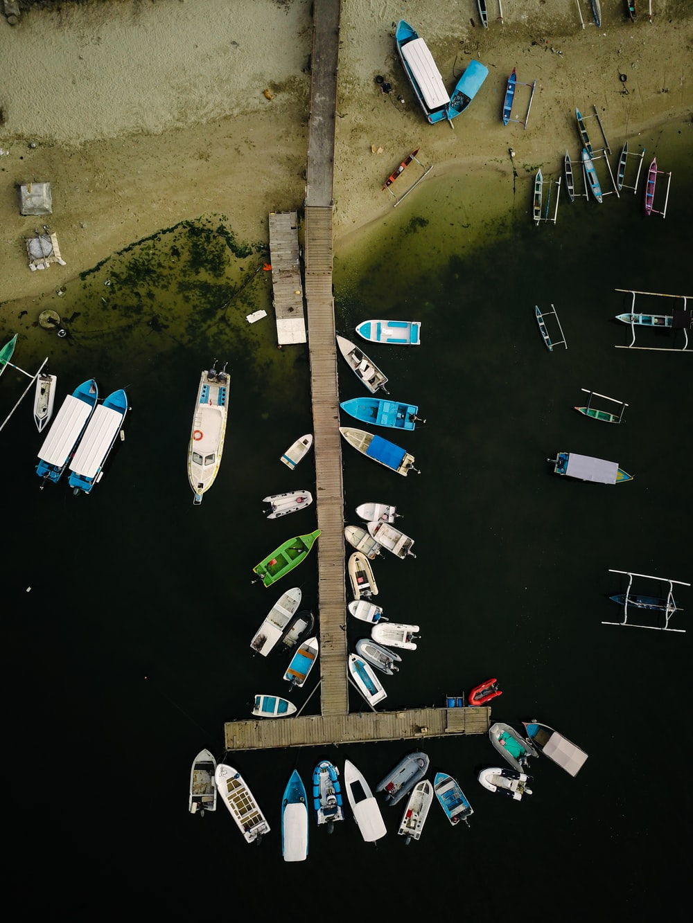 aerial view of motorboats and yachts parked on dock seashore during daytime