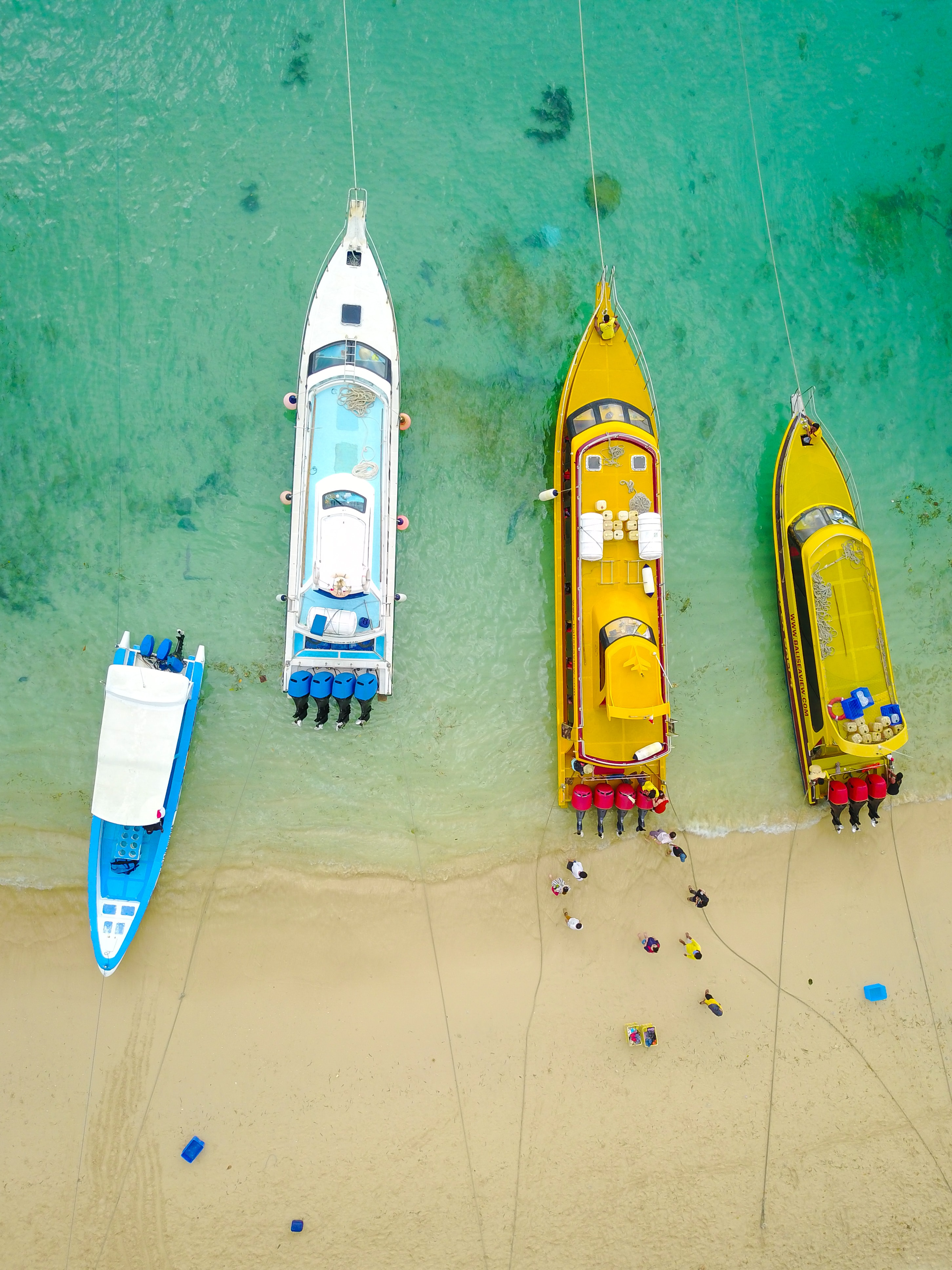 aerial photography of four boats on seashore