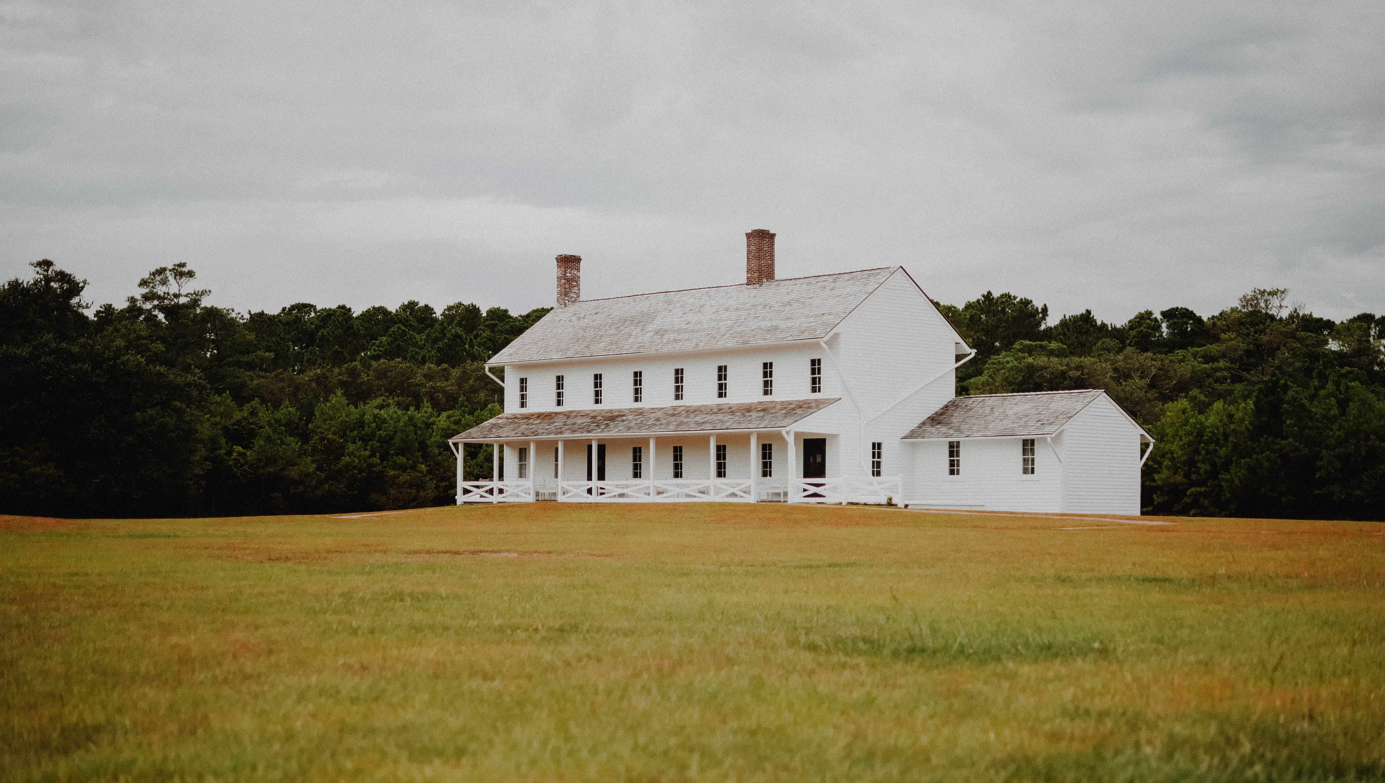white and brown house on green grass field during daytime