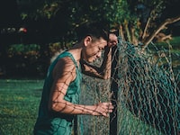 man leaning on green cyclone fence