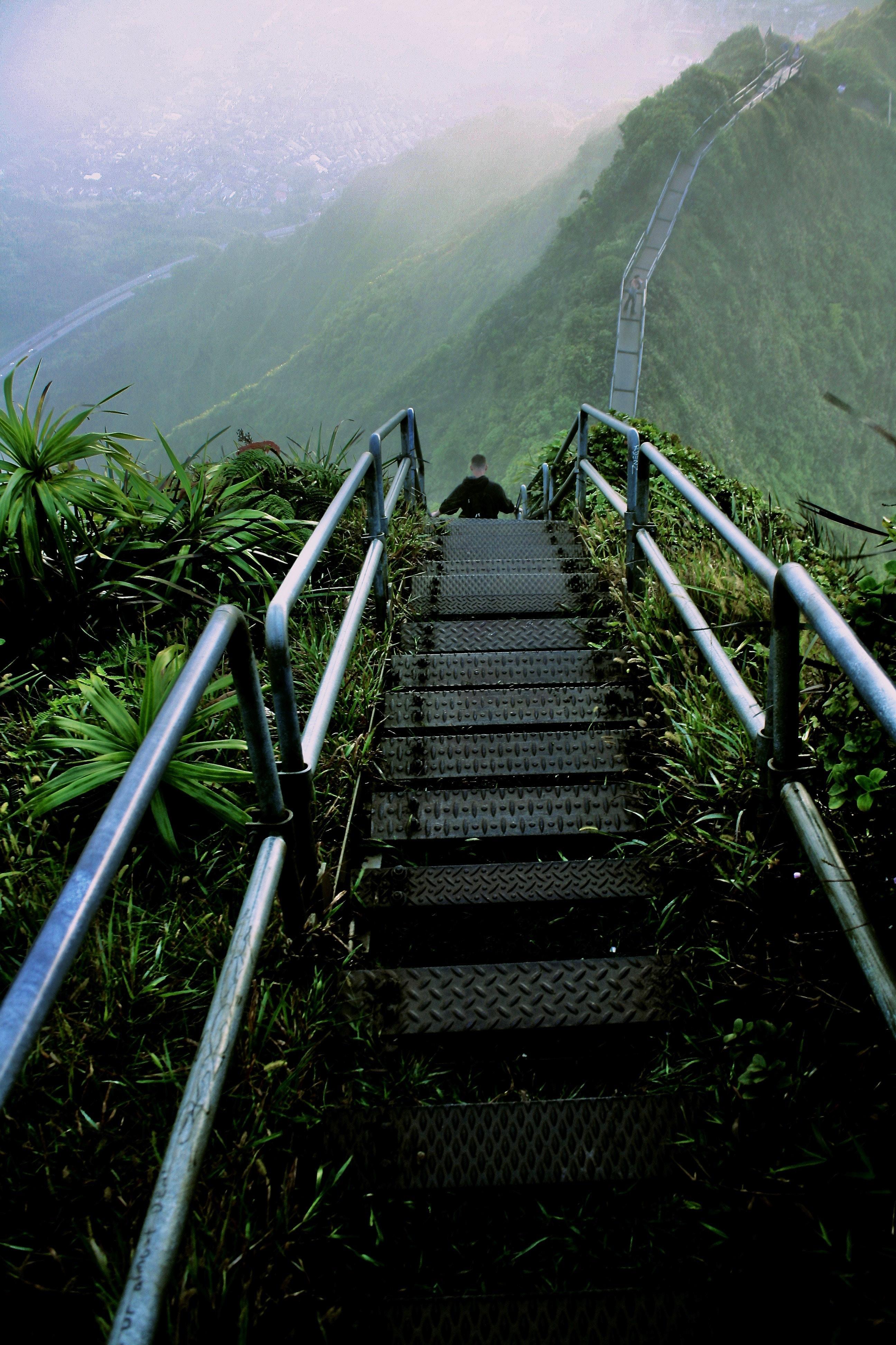 man walking on gray ladder on hill