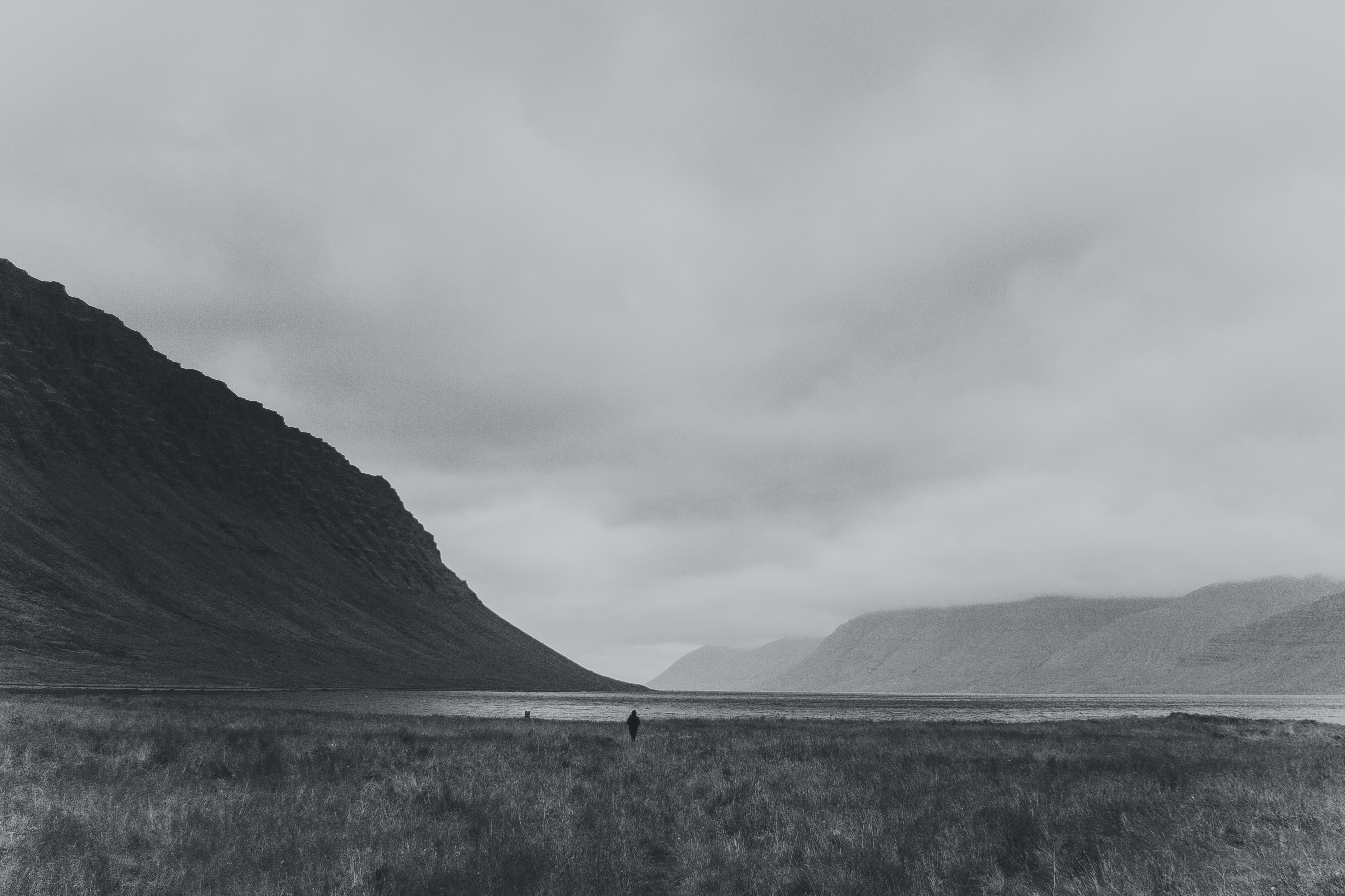 grayscale photo of person standing on open field under sky