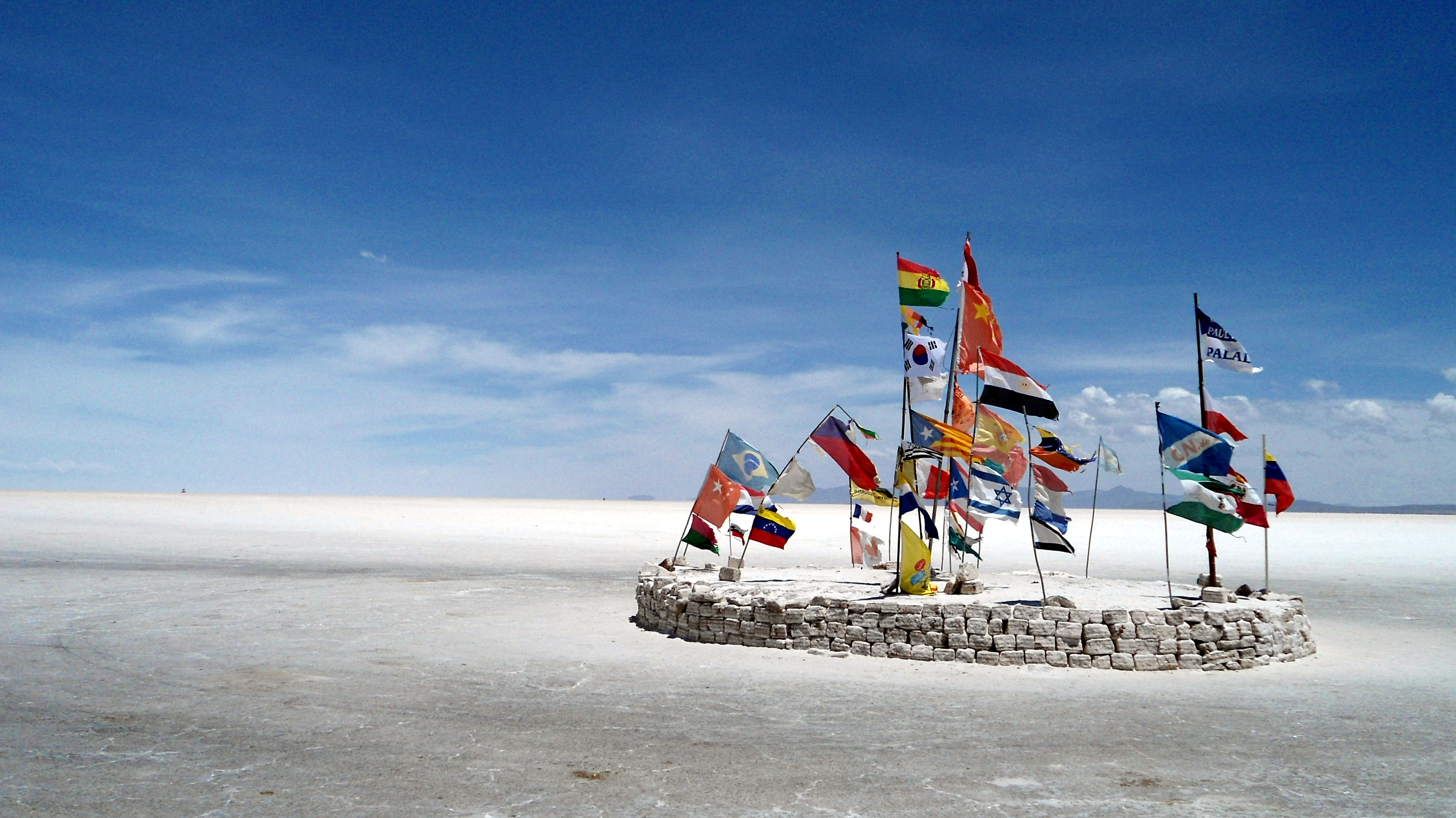 assorted-country flag on gray stones under white clouds at daytime