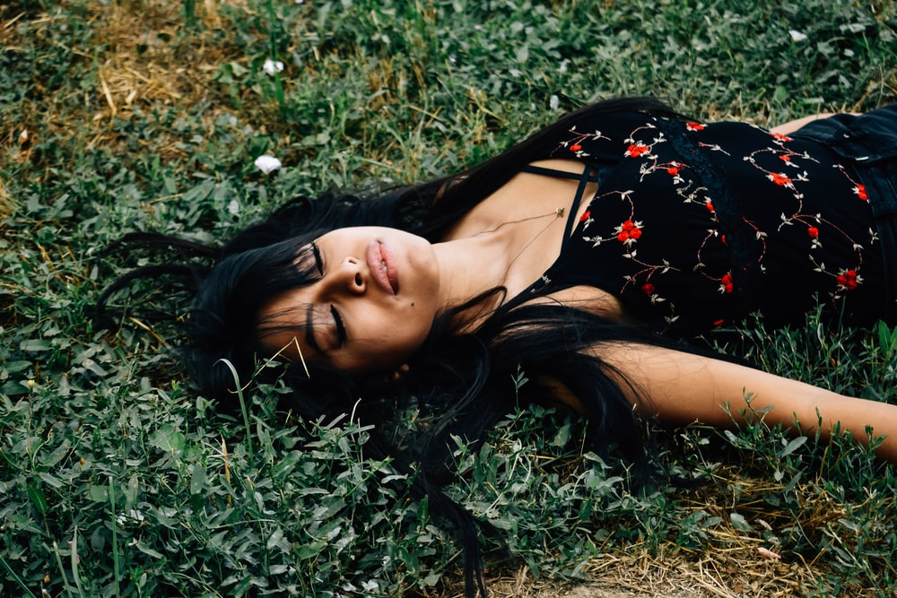 woman lying on ground at daytime