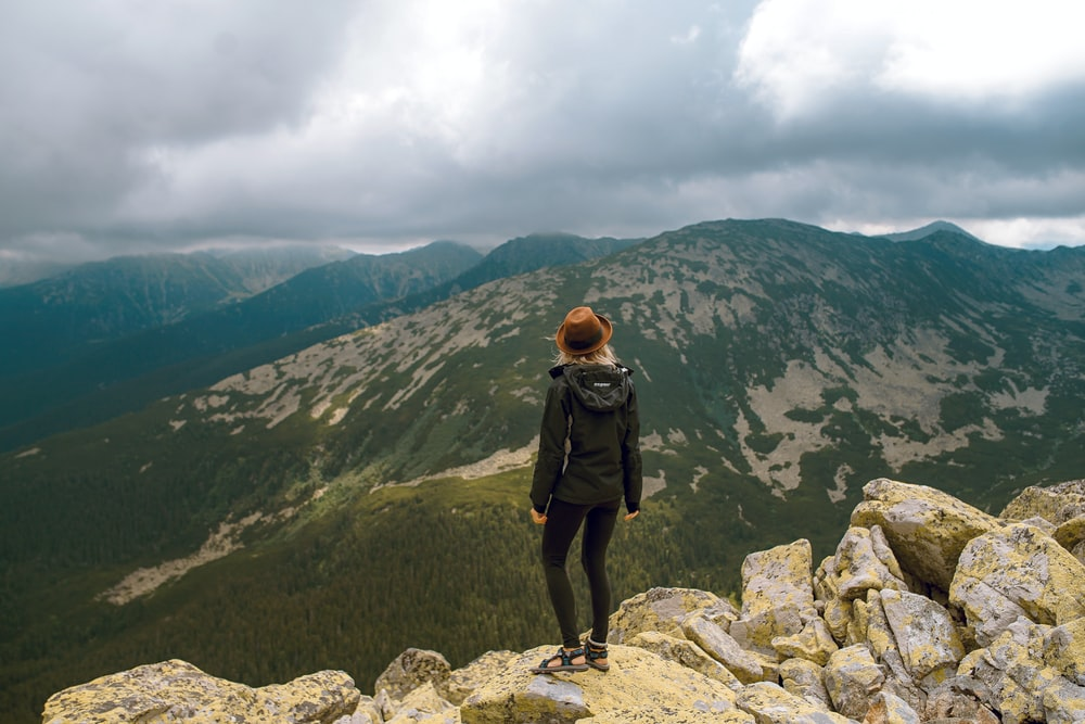 woman standing on rock facing mountains