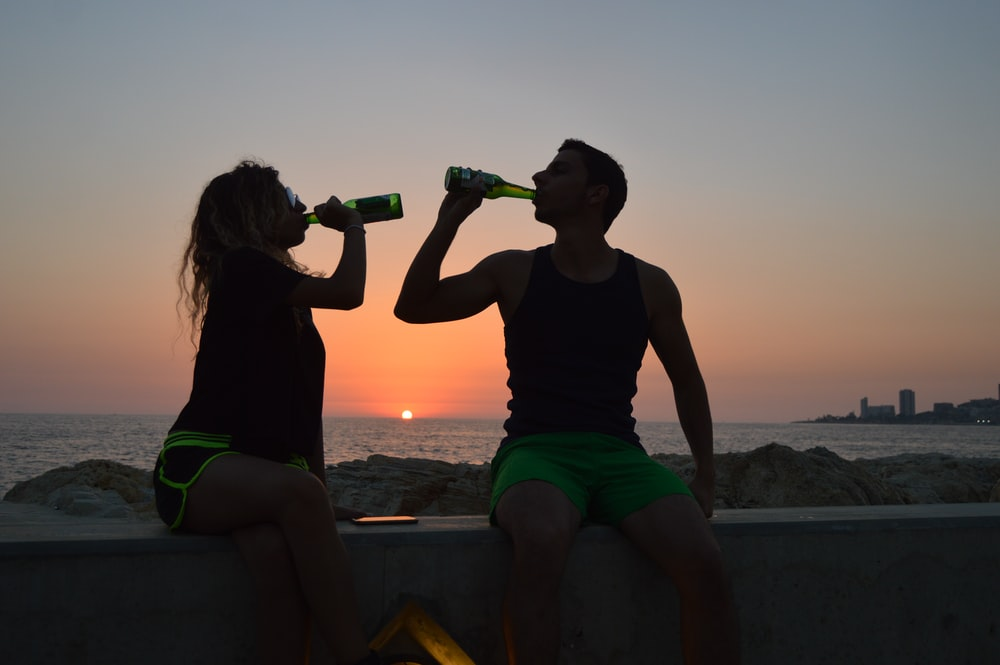 woman and man holding drinking bottles