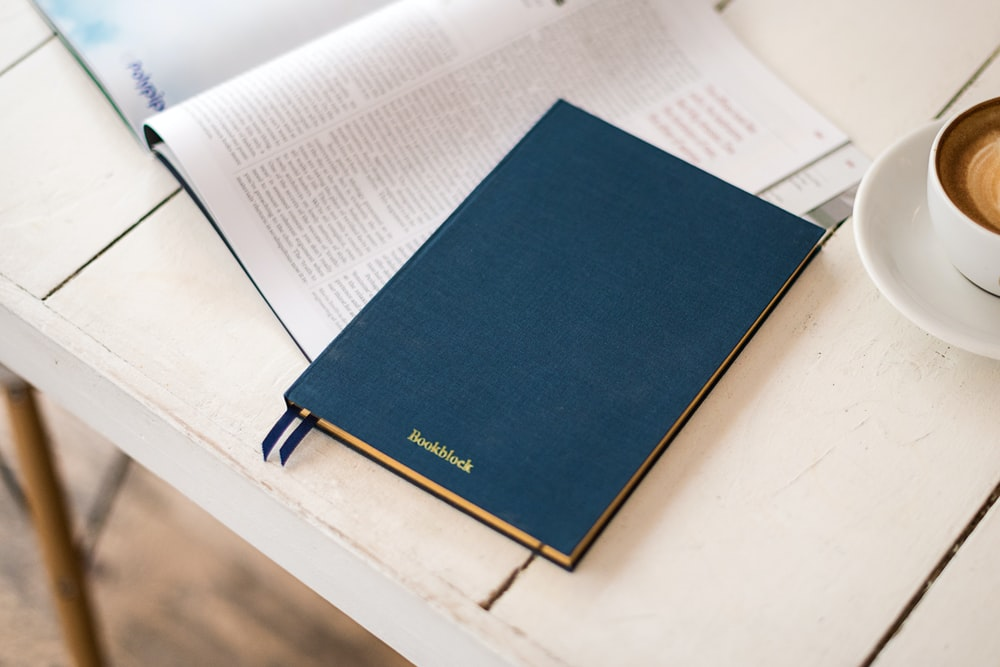 blue hard bind book beside white ceramic coffee cup