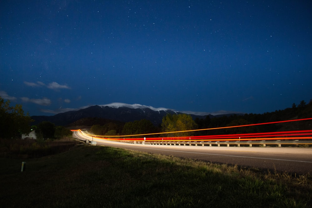 time lapse photograph of train under starry sky