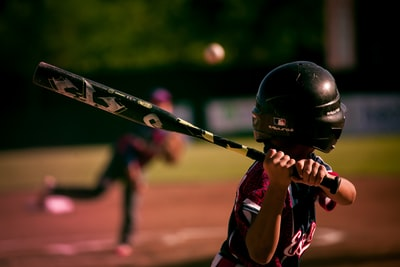 selective focus photography of person holding baseball bat baseball zoom background
