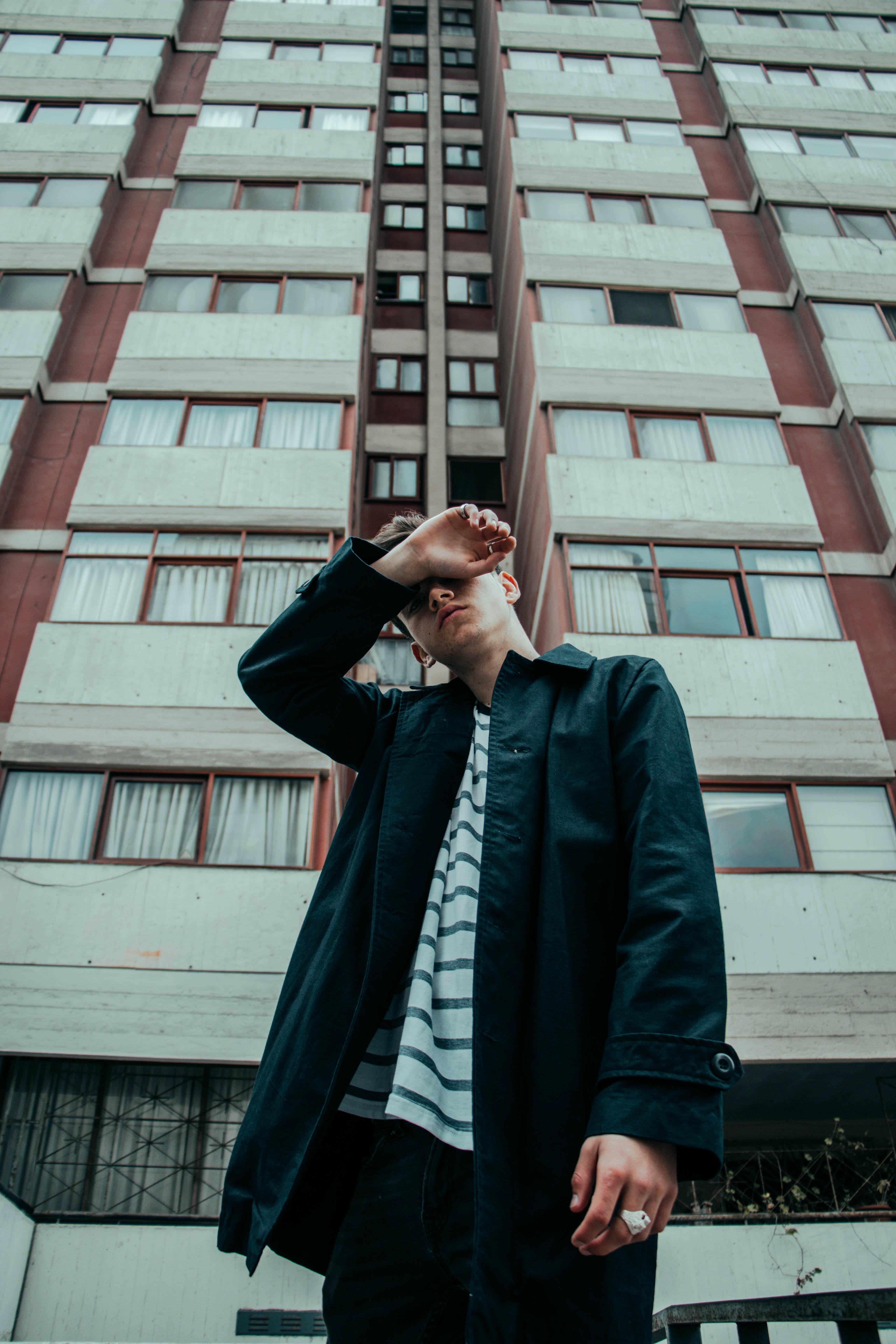 man wearing black jacket standing near building