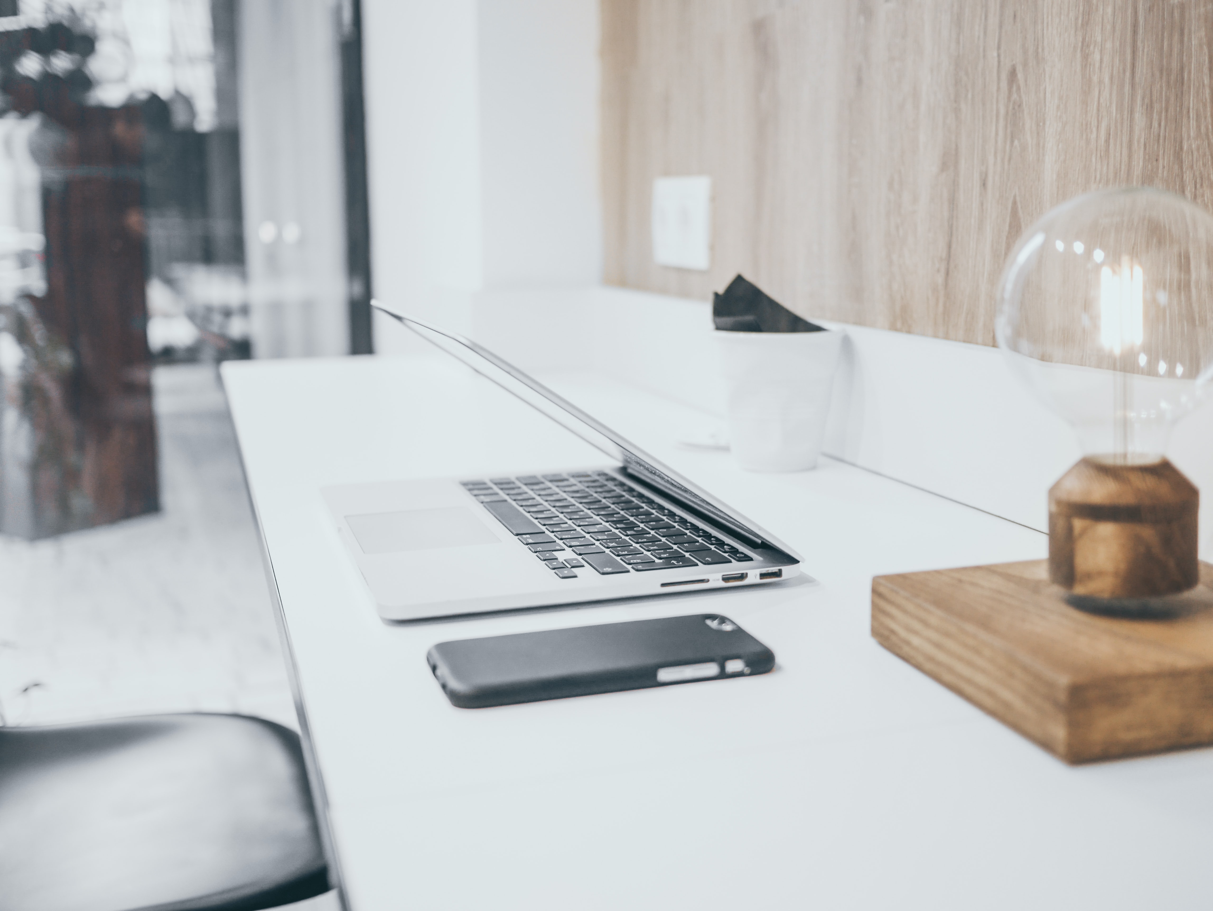 silver MacBook Pro on white table