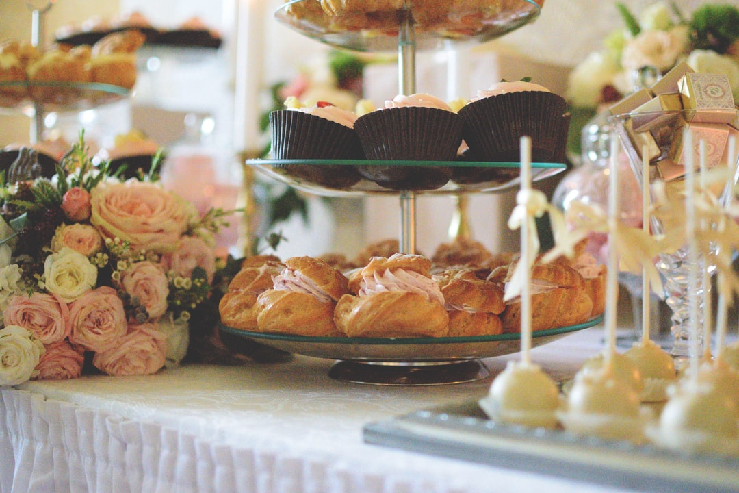 A table featuring flowers and cakes on a cake stand