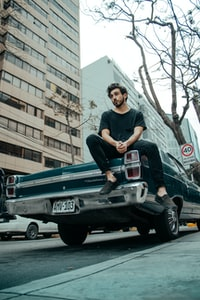 man sitting on classic car