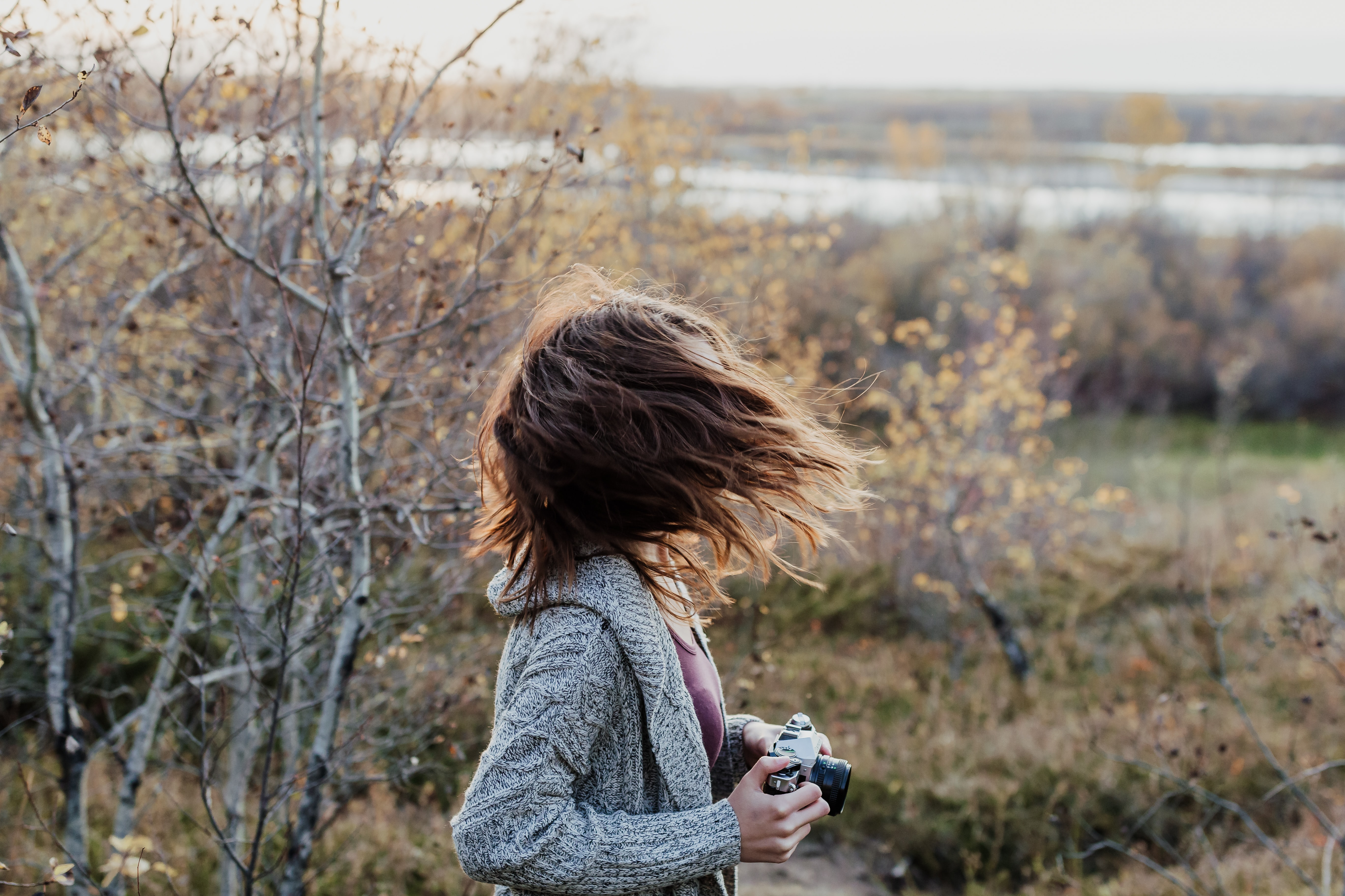 photo of woman waving her hair while holding camera