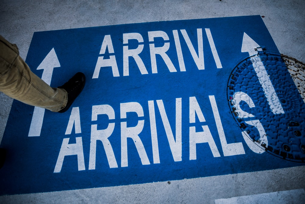 person standing on arrivals sign