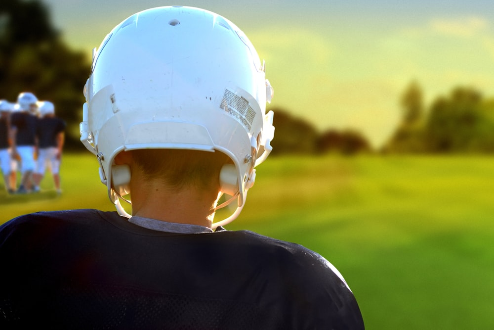 person wearing NFL helmet during daytime