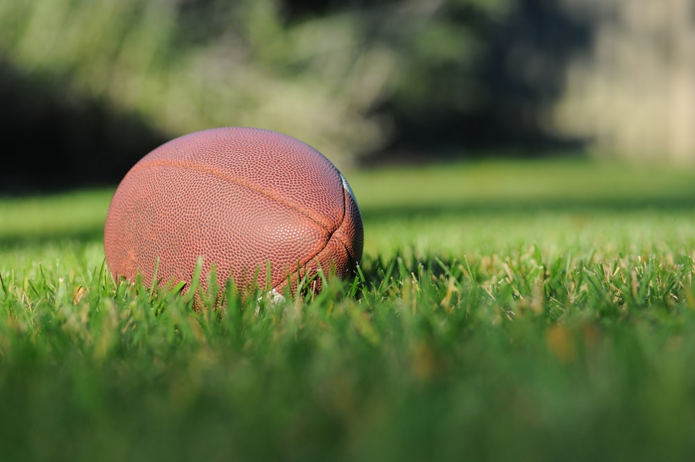 selective focus photography of brown football on grass at daytime