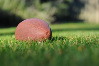 Giants, selective focus photography of brown football on grass at daytime