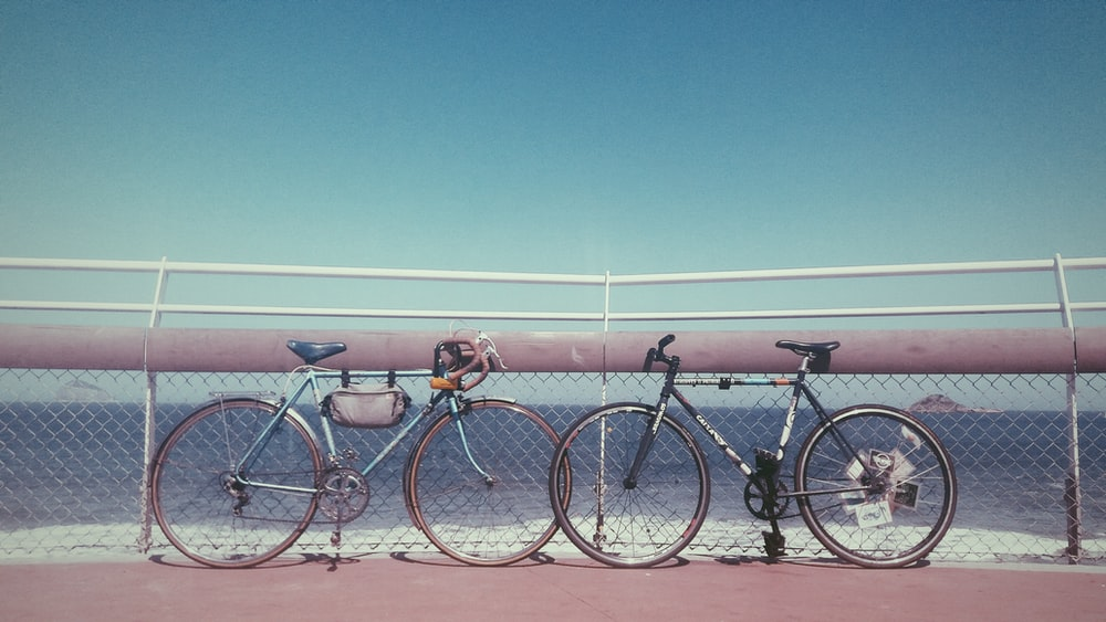two black and gray bicycles parked near fence on seashore at daytime