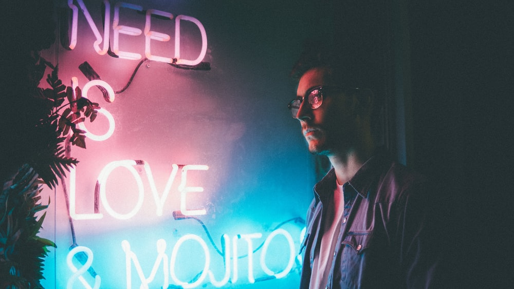 man standing beside white need is love and mojitos neon signage