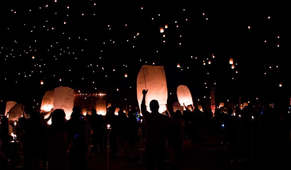 group of people holding lanterns