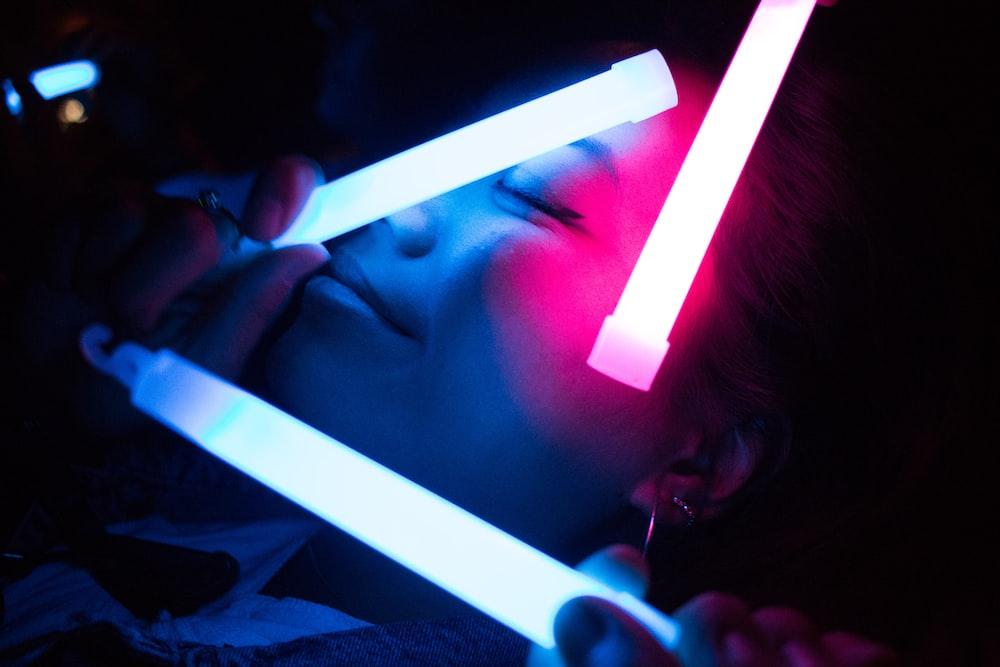 woman holding white LED light inside dark room