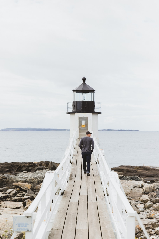 man in gray top walking on dock bridge