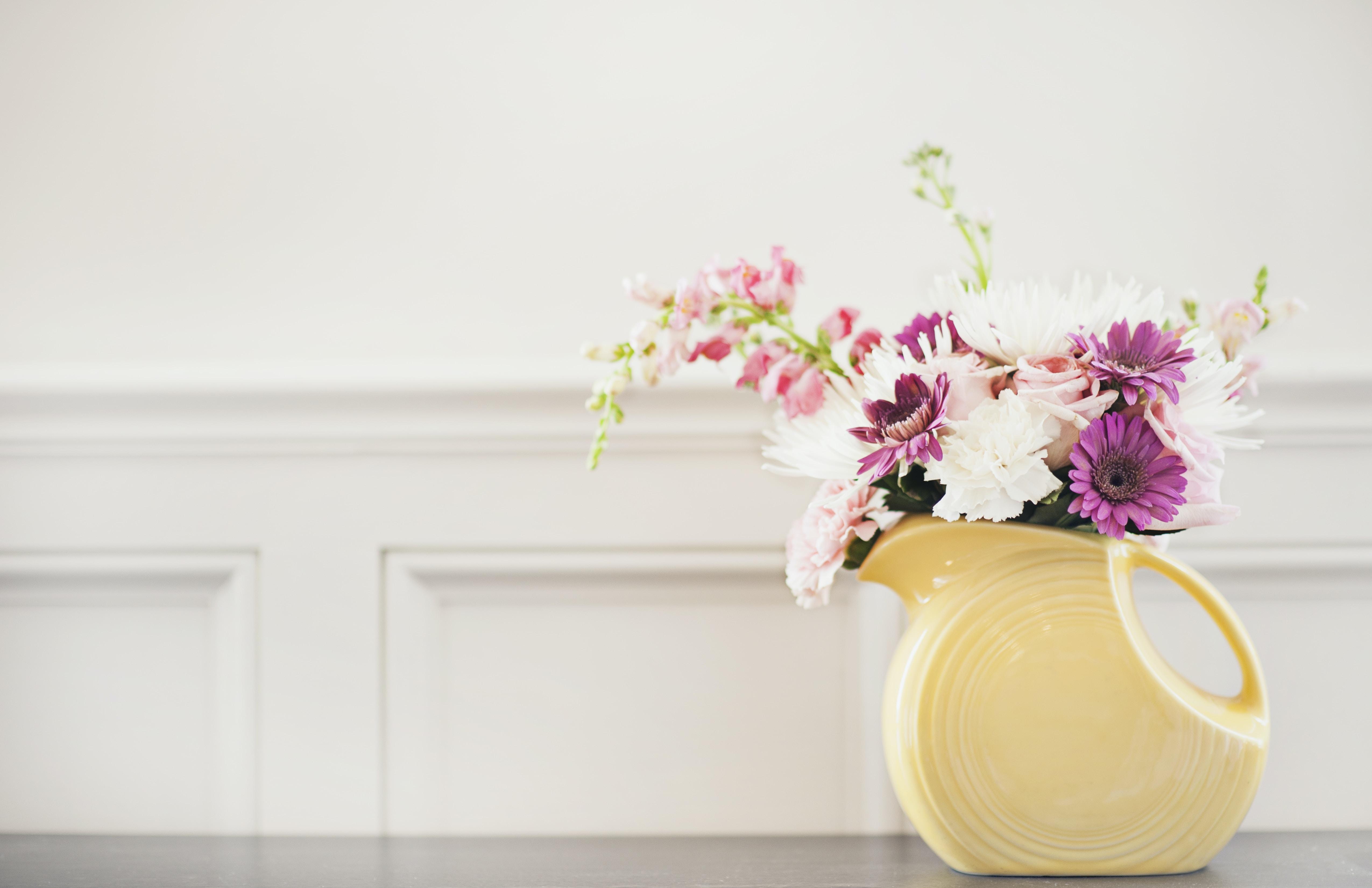 white and purple flowers on white ceramic vase