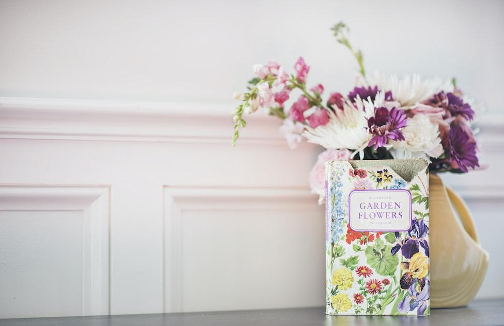 Garden Flowers book beside flower arrangement in vase