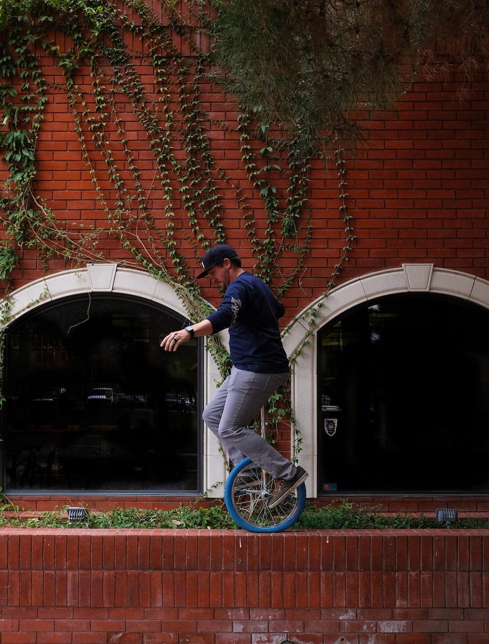 man riding unicycle near wall