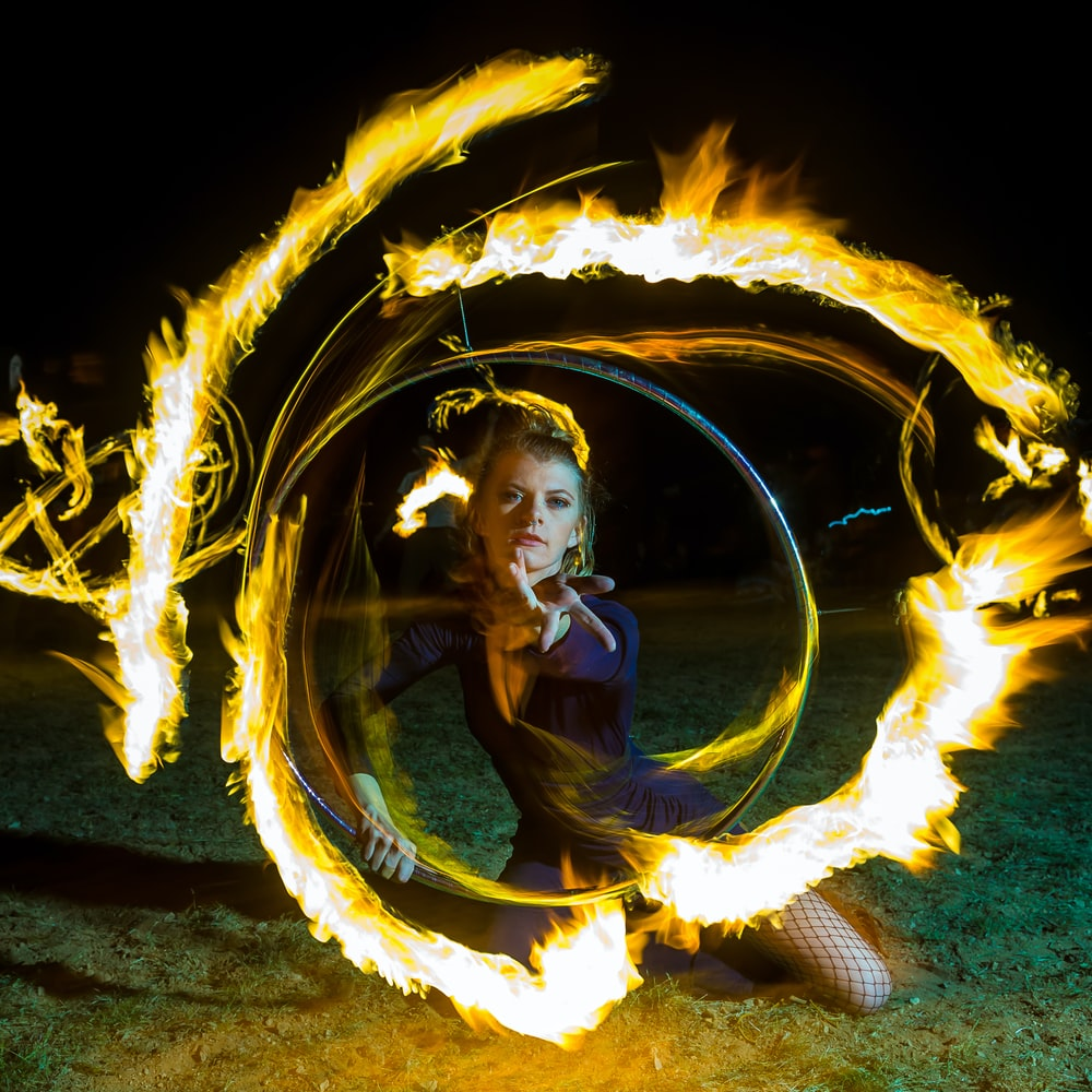 woman kneeling on ground with fire effect