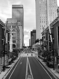 grayscale photo of high-rise buildings near road